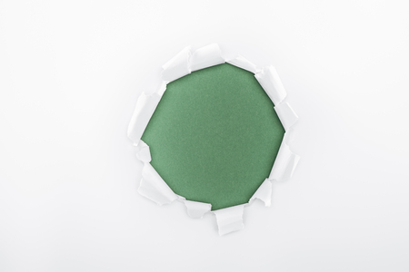 ragged hole in textured white paper on green background