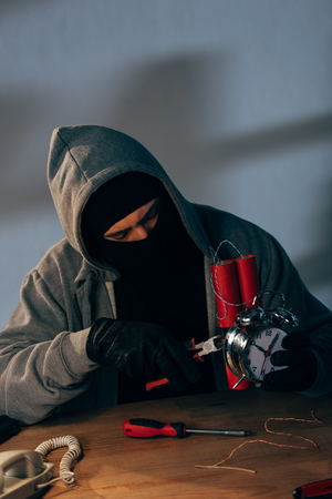 Terrorist in mask and gloves with pliers making bomb
