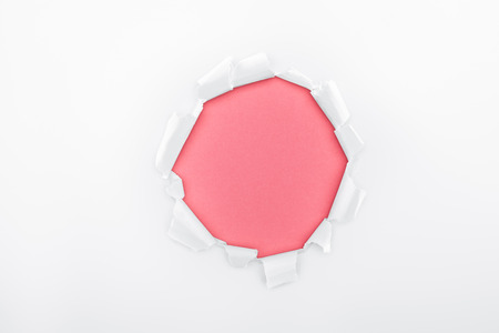 ragged hole in white textured paper on pink background