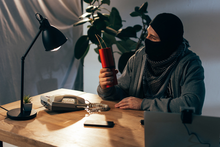 Terrorist in mask sitting in room and holding dynamite