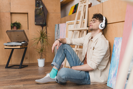 handsome artist in headphones sitting on floor and listening music with closed eyes
