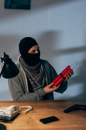 Terrorist in mask holding dynamite while sitting in dark room