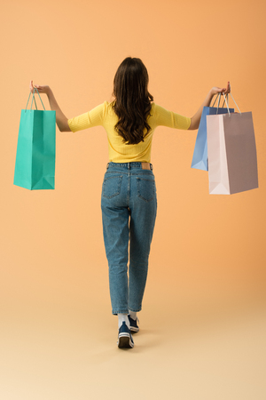 Back view of brunette woman in jeans holding shopping bags on orange background