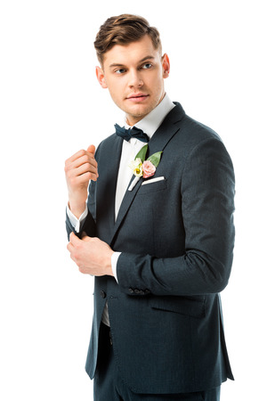 handsome groom in elegant black suite looking away isolated on white
