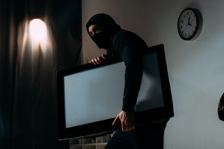 Robber in black mask stealing flat-screen tv with blank screen from apartment
