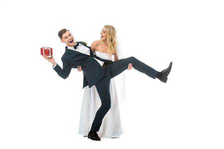excited bride and groom with gift box having fun isolated on white