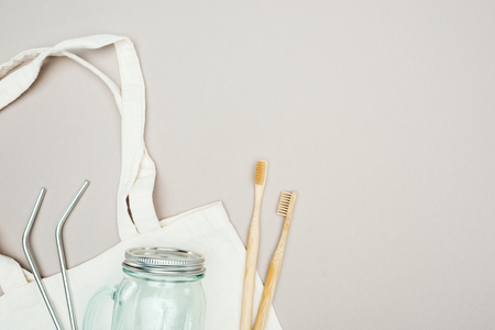 bamboo toothbrushes, reusable stainless steel straws and glass jar on white cotton bag