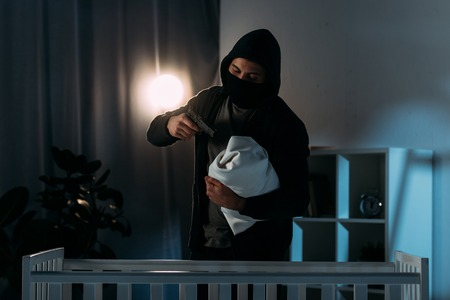 Kidnapper in mask aiming gun at infant child in dark room