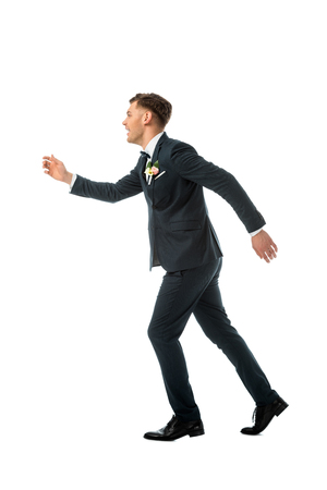 cunning cheerful bridegroom imitating running away isolated on white Stock Photo