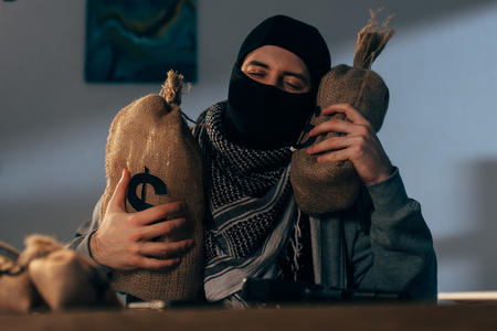 Terrorist in mask holding bags with dollars with closed eyes