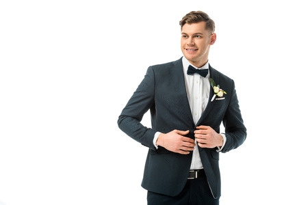 cheerful bridegroom in elegant black jacket with boutonniere isolated on white