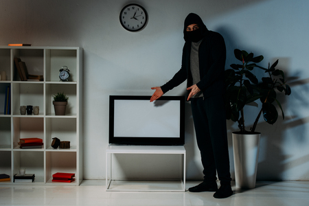 Thief in mask and hoodie pointing with hands at flat-screen tv with blank screen