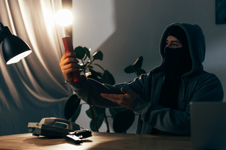Pleased terrorist in mask holding lighted dynamite in room