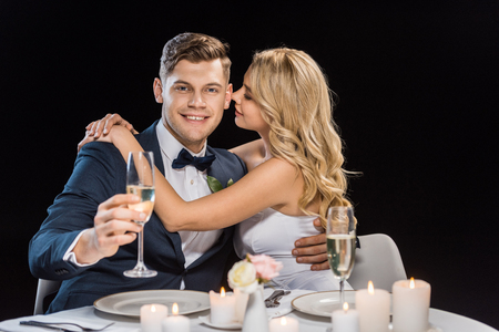 Feliz joven novia abrazando guapo novio con copa de champán aislado en negro Foto de archivo