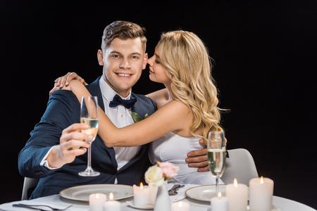 gelukkige jonge bruid omarmen knappe bruidegom met glas champagne geïsoleerd op zwart Stockfoto