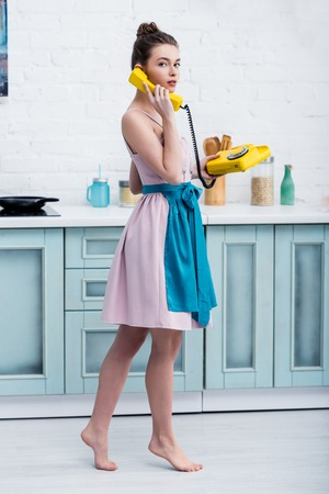 barefoot young woman standing on tiptoe while talking on retro yellow telephone in kitchen