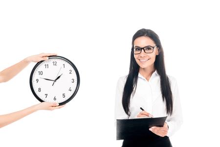Geschäftsfrau mit Brille in Zwischenablage in der Nähe der Uhr schreiben isoliert auf weiß