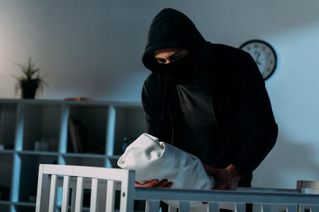 Kidnapper in mask and hoodie standing near crib and holding infant child