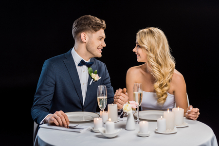 happy young groom and bride holding hands while sitting at served table isolated on black
