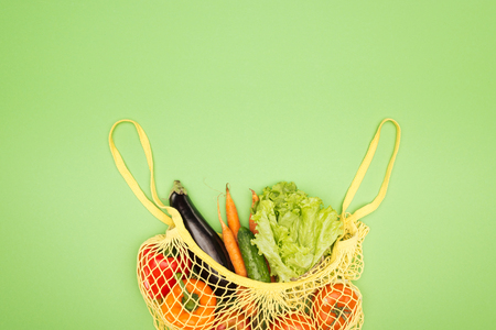 top view of yellow string bag with organic vegetables on light green surface with copy space Фото со стока