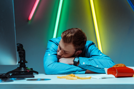 handsome young adult man sleeping and resting on table with joystick and fast food Stock Photo