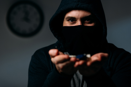 Criminal in hoodie and mask showing keys at camera