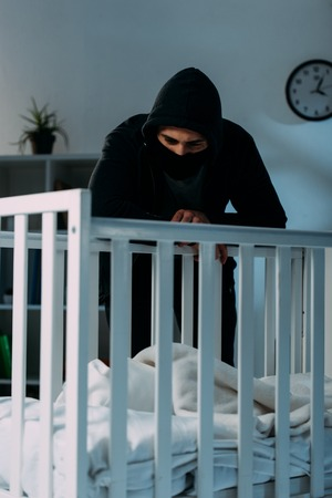 Pensive kidnapper standing in dark room and looking in crib