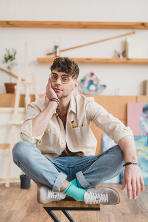 dreamy artist sitting on chair with crossed legs and looking at camera