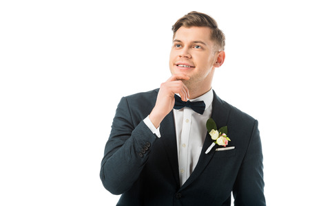 dreamy bridegroom in elegant black suit holding hand near face isolated on white Stock Photo