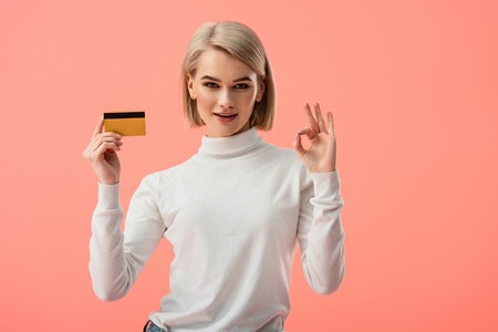 happy blonde young woman holding credit card and showing ok sign isolated on pink Foto de archivo