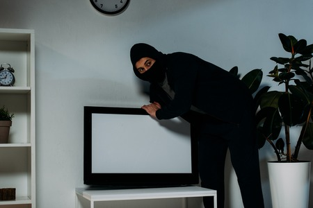 Suspicious robber in mask stealing flat-screen tv with blank screen Stock Photo