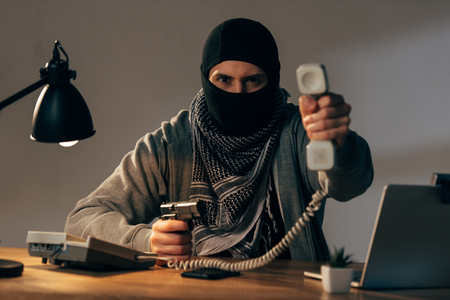 Angry terrorist in black mask holding gun and showing handset at camera