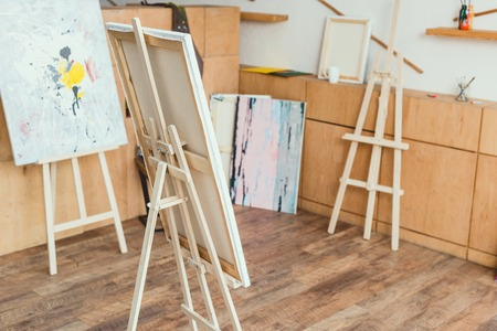 painting studio with wooden floor, cabinets, easels and paintings 免版税图像