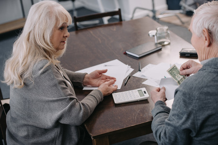 senior couple sitting at table with calculator, money and paperwork