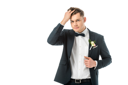 handsome groom in elegant jacket touching hair isolated on white