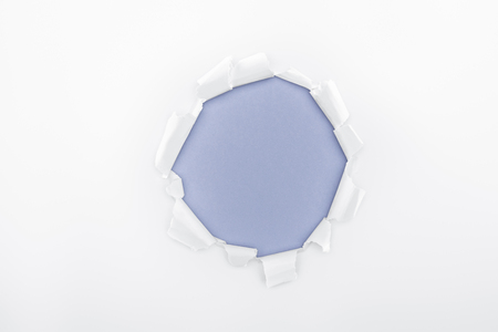 ripped hole in white textured paper on blue background