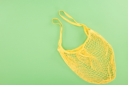 top view of yellow string bag on light green background