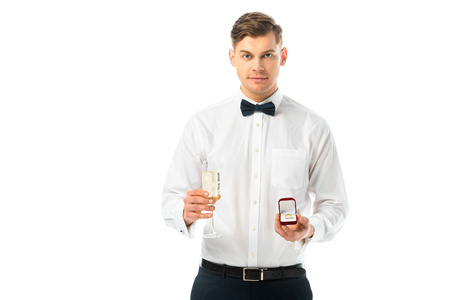 handsome groom holding glass of champagne and gift box with wedding ring isolated on white