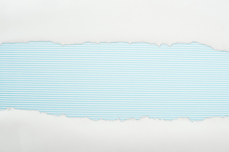 ragged white textured paper with copy space on light blue striped background