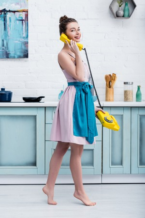 barefoot smiling young woman standing on tiptoe while talking on retro yellow telephone in kitchen Фото со стока - 120050987