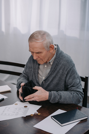 male pensioner sitting at table with paperwork and holding empty wallet Stockfoto