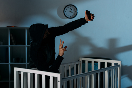 Kidnapper taking selfie near crib and showing peace sign