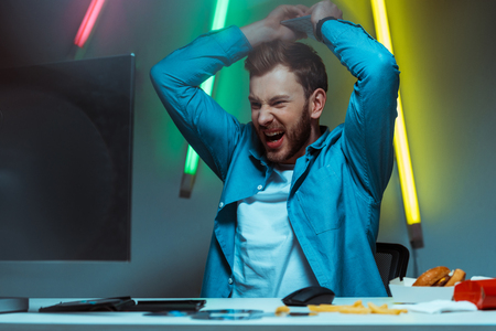 good-looking and angry man holding computer keyboard and screaming Stock Photo