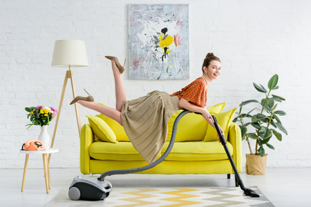 elegant smiling young woman levitating in air and holding vacuum cleaner