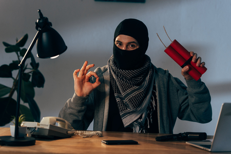 Terrorist in mask holding dynamite and showing okay sign in room