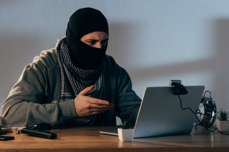 Terrorist in black mask using laptop and looking at webcam