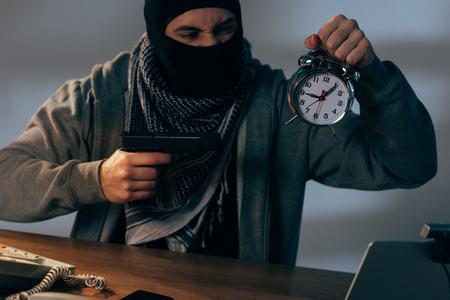 Aggressive terrorist holding gun and alarm clock at table