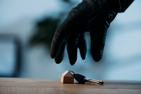 Partial view of thief in leather glove stealing keys Stockfoto