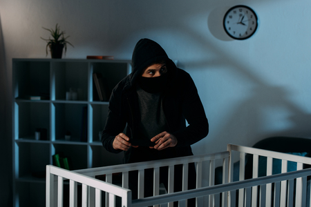 Worried kidnapper in black mask standing near crib and taking picture