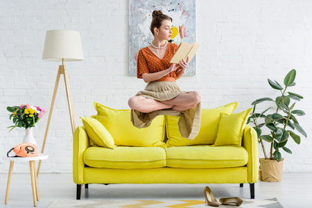 elegant young woman in lotus pose levitating in air while reading book in living room Foto de archivo